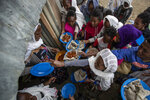 FILE - In this Sunday, May 9, 2021 file photo, displaced Tigrayans line up to receive food donated by local residents at a reception center for the internally displaced in Mekele, in the Tigray region of northern Ethiopia. The United States warned late Thursday, Aug. 19, 2021 that food aid will run out this week for millions of hungry people under a blockade imposed by Ethiopia's government on the embattled Tigray region. (AP Photo/Ben Curtis, File)