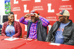 Lafayette High linebacker Eric Jeffries, center, puts on an Ole Miss cap after signing to play football at the University of Mississippi as his mother Antoinette Jeffries, left, and Elliott Hilliard look on during National Signing Day in Oxford, Miss., Wednesday, Dec. 19, 2018. (Bruce Newman, Oxford Eagle via AP)