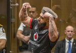 Ahad Nabi gestures as he reads a victim impact statement during the sentencing hearing for Australian Brenton Harrison Tarrant at the Christchurch High Court after Tarrant pleaded guilty to 51 counts of murder, 40 counts of attempted murder and one count of terrorism in Christchurch, New Zealand, Wednesday, Aug. 26, 2020. More than 60 survivors and family members will confront the New Zealand mosque gunman this week when he appears in court to be sentenced for his crimes in the worst atrocity in the nation's modern history. (John Kirk-Anderson/Pool Photo via AP)