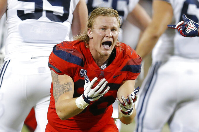 FILE - In this Sept. 1, 2018, file photo, Arizona defensive end Justin Belknap gestures in the first half during an NCAA college football game against Brigham Young, in Tucson, Ariz. Arizona was supposed to make a seamless transition to new coach Kevin Sumlin, possibly contend for a Pac-12 South title. Through two games, the Wildcats have done little but struggle under their first-year coach. (AP Photo/Rick Scuteri, File)
