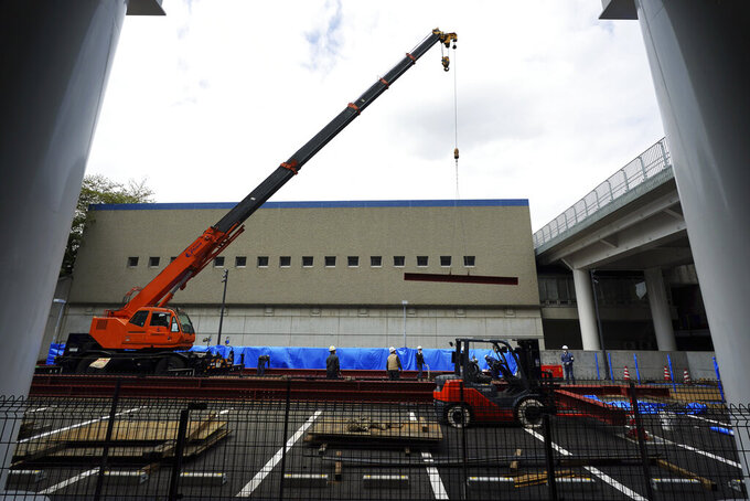 Construction workers lift a steel beam into position at Tokyo Metropolitan Gymnasium, one of venues for the postponed Tokyo 2020 Olympics Tuesday, April 6, 2021, in Tokyo. Many preparations are still up in the air as organizers try to figure out how to hold the postponed games in the middle of a pandemic. (AP Photo/Eugene Hoshiko)