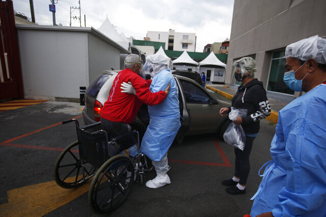 A health worker helps Luis Reyes into a car, to be taken home after recovering from COVID-19, outside the Mexico City Ajusco Medio General Hospital, Wednesday, Dec. 2. 2020. Mexico continues to report an increase in the number of coronavirus cases, with Mexico City continuing to report the biggest portion of the surge. (AP Photo/Marco Ugarte)