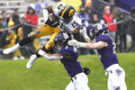 Iowa running back Tyler Goodson (15) is pushed out of bounds by Northwestern defensive back Greg Newsome II, center, and linebacker Chris Bergin, right, during the second half of an NCAA college football game, Saturday, Oct. 26, 2019, in Evanston, Ill. (AP Photo/David Banks)