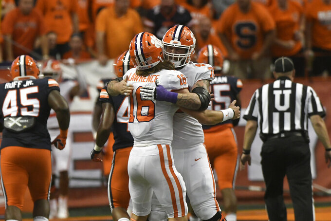 Clemson quarterback Trevor Lawrence (16) is congratulated by Chandler Reeves after a score against Syracuse during the first quarter of an NCAA college football game Saturday, Sept. 14, 2019, in Syracuse, N.Y. (AP Photo/Steve Jacobs)