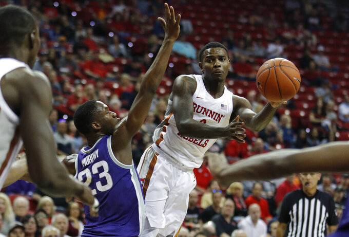 UNLV's Amauri Hardy passes around Kansas State's Montavious Murphy (23) during the first half of an NCAA college basketball game Saturday, Nov. 9, 2019, in Las Vegas. (AP Photo/John Locher)