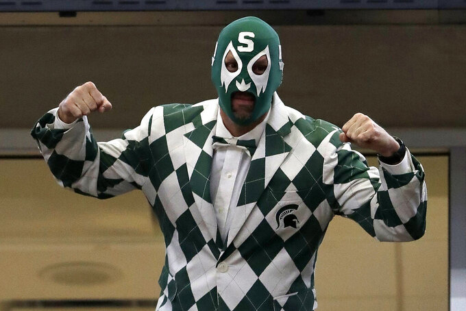 A Michigan State fan poses as he cheer during the first half of an NCAA college basketball game between Michigan State and Wisconsin in the semifinals of the Big Ten Conference tournament, Saturday, March 16, 2019, in Chicago. (AP Photo/Nam Y. Huh)