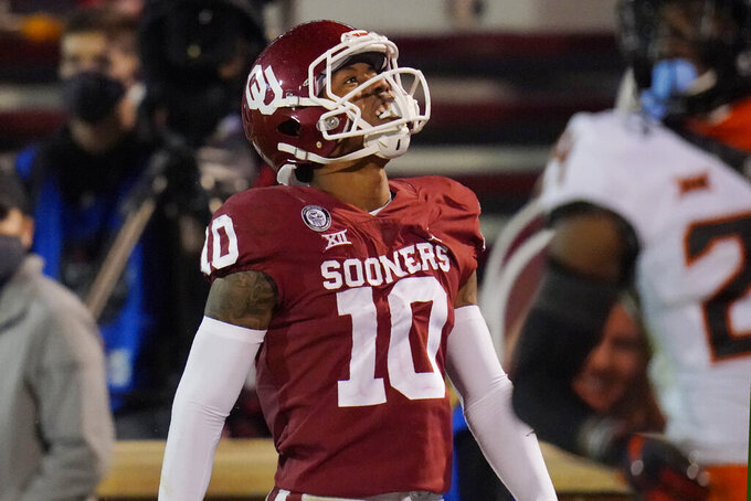 Oklahoma wide receiver Theo Wease (10) celebrates a touchdown against Oklahoma State during the second half of an NCAA college football game in Norman, Okla., Saturday, Nov. 21, 2020. (AP Photo/Sue Ogrocki)