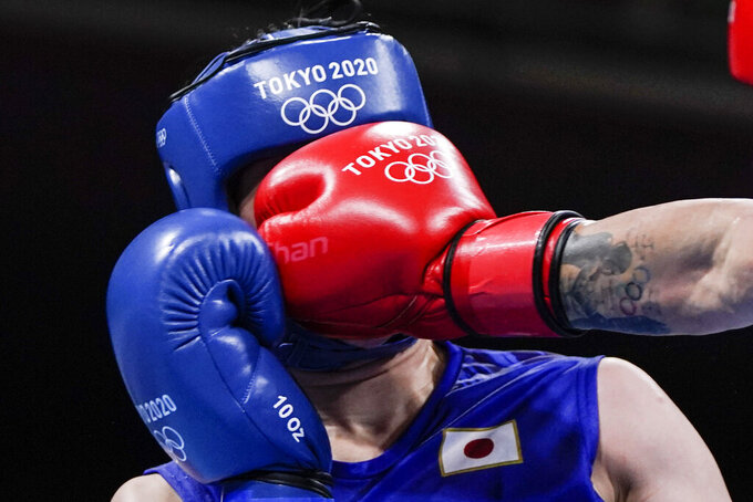 Romania's Maria Nechita, right, punches Japan's Sena Irie during their women's featherweight 57-kg boxing match at the 2020 Summer Olympics, Wednesday, July 28, 2021, in Tokyo, Japan. (AP Photo/Frank Franklin II, Pool)