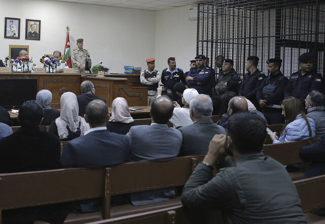 Israeli Konstantin Kotov stands in the defendant's cage during an appearance before a state security court where he was charged with illegally entering the country and possessing drugs, in Amman, Jordan, Monday Dec. 2, 2019. Kotov pleaded guilty on Monday to entering Jordan illegally but denied the other charge. The judge rejected his argument that possessing a small amount of marijuana is legal in Israel. (AP Photo/Raad Adayleh)