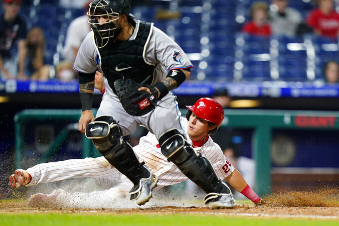 Philadelphia Phillies' Nick Maton, right, scores past Miami Marlins catcher Sandy Leon on a single by Jean Segura during the eighth inning of a baseball game, Tuesday, May 18, 2021, in Philadelphia. (AP Photo/Matt Slocum)