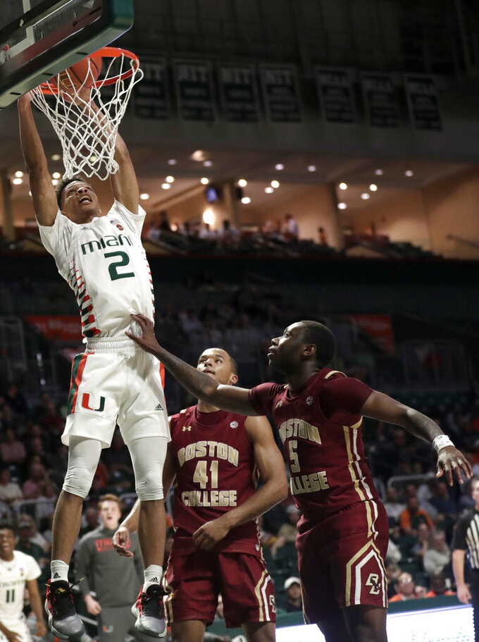 Miami guard Isaiah Wong (2) dunks over Boston College forward Steffon Mitchell (41) and guard Jay Heath (5) during the second half of an NCAA college basketball game, Wednesday, Feb. 12, 2020, in Coral Gables, Fla. Miami won 85-58. (AP Photo/Lynne Sladky)