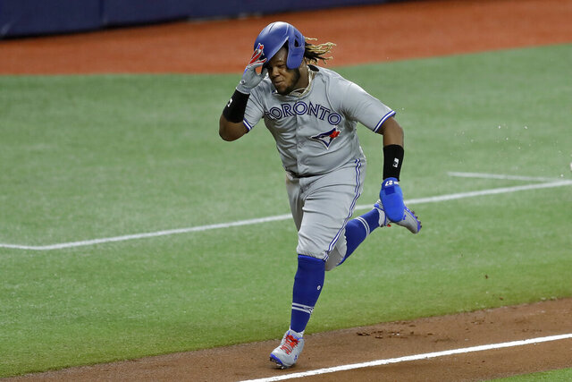 Toronto Blue Jays' Vladimir Guerrero Jr. races home to score on a sacrifice fly by Rowdy Tellez off Tampa Bay Rays starting pitcher Charlie Morton during the fourth inning of a baseball game Friday, July 24, 2020, in St. Petersburg, Fla. (AP Photo/Chris O'Meara)