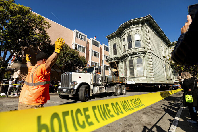 A worker signals to a truck driver pulling a Victorian home through San Francisco on Sunday, Feb. 21, 2021. The house, built in 1882, was moved to a new location about six blocks away to make room for a condominium development. According to the consultant overseeing the project, the move cost approximately $200,000 and involved removing street lights, parking meters, and utility lines. (AP Photo/Noah Berger)