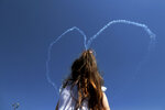A girl sits on her father's shoulders as they watch the Turkish acrobatic aircraft jets make a heart sign in the sky, during a military parade celebration marking the 45th anniversary of the 1974 Turkish invasion in the Turkish occupied area of the divided capital Nicosia, Cyprus, Saturday, July 20, 2019. Cyprus was split into Greek Cypriot south and Turkish Cypriot north in 1974 when Turkey invaded in response to a coup by supporters of a union with Greece. (AP Photo/Petros Karadjias)
