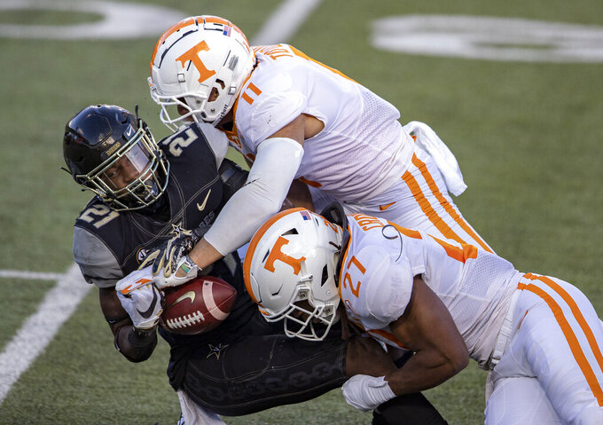 Vanderbilt's Keyon Henry-Brooks is tackled by Tennessee linebacker Henry To'o To'o (11) and linebacker Quavaris Crouch (27) during the first half of an NCAA college football game Saturday, Dec. 12, 2020, in Nashville, Tenn. (AP Photo/Wade Payne)