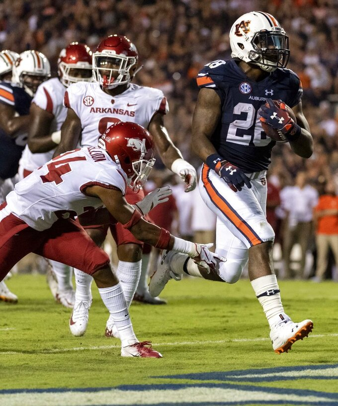 Auburn running back JaTarvious Whitlow (28) scores a running touchdown past Arkansas defensive back Jarques McClellion (24) during the first half of an NCAA college football game, Saturday, Sept. 22, 2018, in Auburn, Ala. (AP Photo/Vasha Hunt)