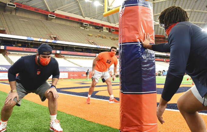 Syracuse offensive lineman Airon Servais, left, and Carlos Vettorello (52) warm up before an NCAA college football game against Liberty on Saturday, Oct 17, 2020, at the Carrier Dome in Syracuse, N.Y.  (Dennis Nett/The Post-Standard via AP)