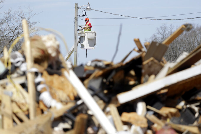 In this March 26, 2020, photo, a utility worker repairs a power line in Cookeville, Tenn. People still reeling from the deadly twisters that hit the state on March 3 now have to confront life in the age of coronavirus. (AP Photo/Mark Humphrey)