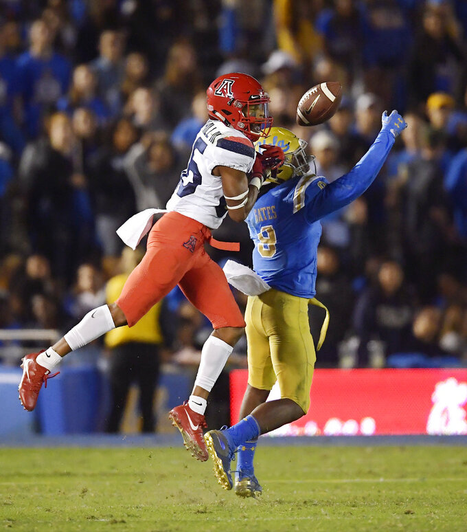UCLA defensive back Elijah Gates, right, intercepts a pass intended for Arizona wide receiver Stanley Berryhill III during the second half of an NCAA college football game Saturday, Oct. 20, 2018, in Pasadena, Calif. UCLA won 31-30. (AP Photo/Mark J. Terrill)