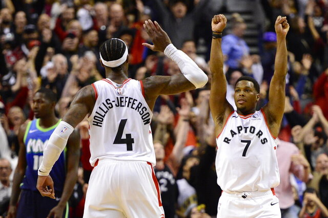Toronto Raptors guard Kyle Lowry (7) and teammate forward Rondae Hollis-Jefferson (4) celebrate after defeating the Dallas Mavericks in NBA basketball game action in Toronto, Sunday, Dec. 22, 2019. (Frank Gunn/The Canadian Press via AP)
