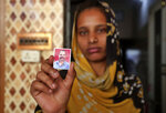 In this Tuesday, Feb. 11, 2020 photo, Zeel Makwana displays a photograph of her father Bhalabhai Makwana, one of the victims of Saturday's fire at Nandan Denim garment factory, one of the largest denim suppliers in the world, in Ahmedabad, India. At least seven people died when a blaze swept a garment factory that made jeans for some of the world's most popular brands, the tragedy illustrating the risks faced by workers at some workplaces that cater raw material to popular fashion brands but lack necessary clearances and fire safety equipment. Local safety and health authorities have asked the company to close until further notice. Its licenses have been suspended, and Nandan Denim has agreed to pay the families of those killed a reported $14,000 each. (AP Photo/Ajit Solanki)