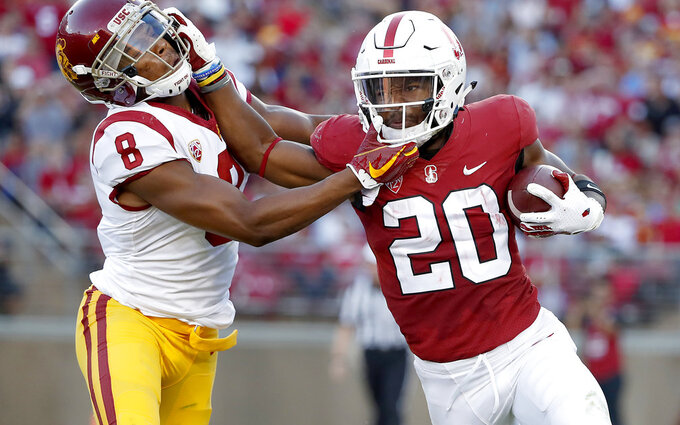FILE - In this Saturday, Sept. 8, 2018 file photo, Stanford running back Bryce Love (20) stiff-arms Southern California cornerback Iman Marshall (8) during the first half of an NCAA college football game in Stanford, Calif. Stanford will get star running back Bryce Love back for this week's Pac-12 North showdown against No. 20 Oregon but the seventh-ranked Cardinal will be without a key defensive player. (AP Photo/Tony Avelar, File)