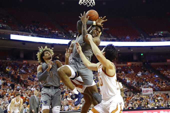West Virginia forward Derek Culver (1) battle for a rebound over Texas forward Brock Cunningham (30) during the second half of an NCAA college basketball game, Monday, Feb. 24, 2020, in Austin, Texas. (AP Photo/Eric Gay)
