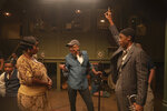 This image released by Netflix shows Viola Davis as Ma Rainey, left, director George C. Wolfe, center, and Chadwick Boseman as Levee during the filming of