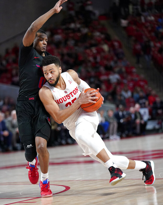 Houston's Galen Robinson Jr. (25) drives around Southern Methodist's Jahmal McMurray (0) during the second half of an NCAA college basketball game Thursday, March 7, 2019, in Houston. Houston won 90-79 to clinch a share of the American Athletic Conference Championship. (AP Photo/David J. Phillip)
