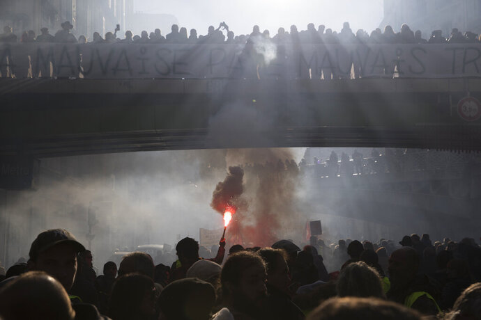 A striker lights a flare during a demonstration Thursday, Jan. 9, 2020 in Marseille, southern France. Rail workers, teachers, doctors, lawyers and others joined a nationwide day of protests and strikes Thursday to denounce French President Emmanuel Macron's plans to overhaul the pension system. (AP Photo/Daniel Cole)