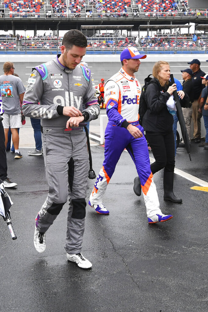 Alex Bowman, left, and Denny Hamlin leave pit row after a NASCAR Cup series auto race is postponed until Monday due to rain Sunday, Oct. 3, 2021, in Talladega, Ala. (AP Photo/John Amis)