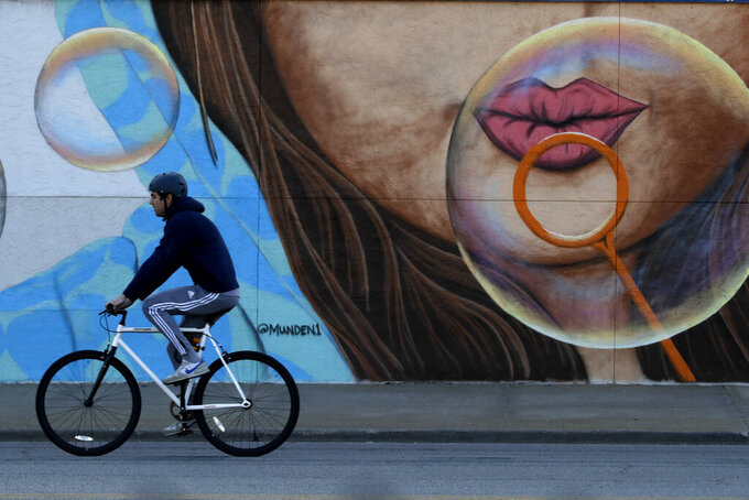A man rides his bicycle past a mural in Kansas City, Mo. Wednesday, April 15, 2020, as stay-at-home orders continue in the state as part of an effort to curb the spread of the new coronavirus. (AP Photo/Charlie Riedel)