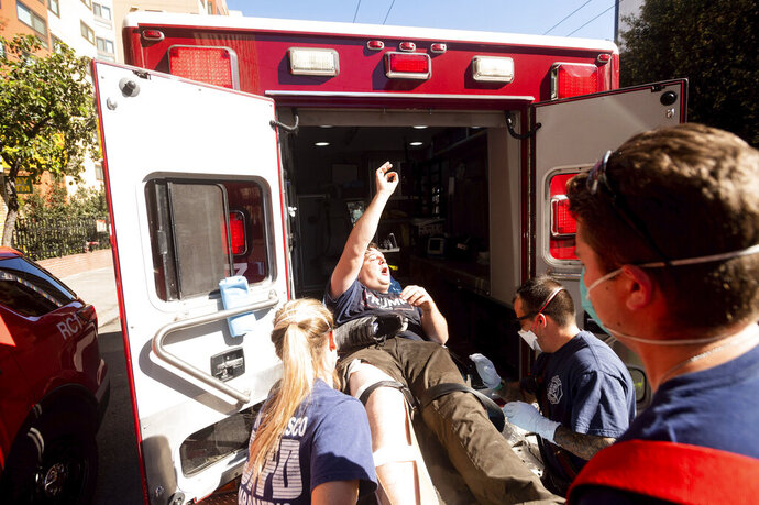 Medics transport a supporter of President Donald Trump to an ambulance after he was attacked by counter-protesters in San Francisco on Saturday, Oct. 17, 2020. About a dozen pro-Trump demonstrators were met by several hundred counter-protesters as they tried to rally. (AP Photo/Noah Berger)