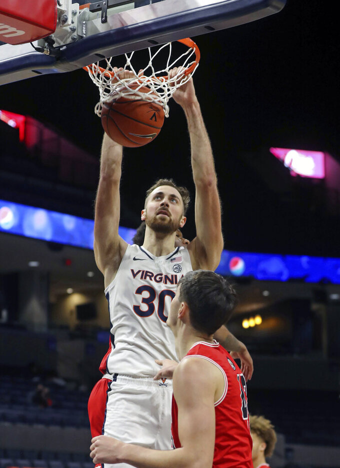 Virginia forward Jay Huff (30) dunks the ball in front of St. Francis forward Mark Flagg (42) during an NCAA college basketball game, Tuesday, Dec. 1, 2020 in Charlottesville, Va. (Andrew Shurleff/The Daily Progress via AP)