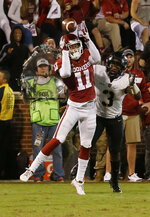 Oklahoma cornerback Parnell Motley (11) intercepts a pass intended for Army running back Jordan Asberry (3) in overtime of an NCAA college football game in Norman, Okla., Saturday, Sept. 22, 2018. Oklahoma won 28-21 in overtime. (AP Photo/Sue Ogrocki)