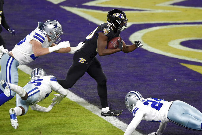 Baltimore Ravens wide receiver Miles Boykin, center, scores on a touchdown catch and run as Dallas Cowboys outside linebacker Leighton Vander Esch (55), free safety Xavier Woods (25) and cornerback Chidobe Awuzie (24) try to stop him during the first half of an NFL football game, Tuesday, Dec. 8, 2020, in Baltimore. (AP Photo/Gail Burton)