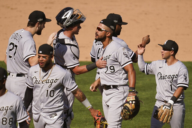 Chicago White Sox's Lucas Giolito, clockwise from top left, celebrates with James McCann, Jose Abreu, Alex Colome, Nick Madrigal and Yoan Moncada (10) after the White Sox defeated the Oakland Athletics in Game 1 of an American League wild-card baseball series Tuesday, Sept. 29, 2020, in Oakland, Calif. (AP Photo/Eric Risberg)