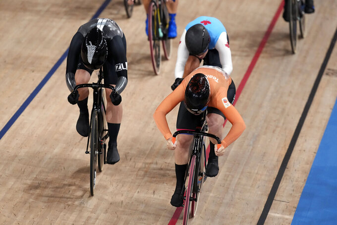 Shanne Braspennincx of Team Netherlands crosses the line to win the gold medal as Ellesse Andrews of Team New Zealand, left, wins silver and Lauriane Genest of Team Canada wins bronze, during the track cycling women's keirin at the 2020 Summer Olympics, Thursday, Aug. 5, 2021, in Izu, Japan. (AP Photo/Christophe Ena)
