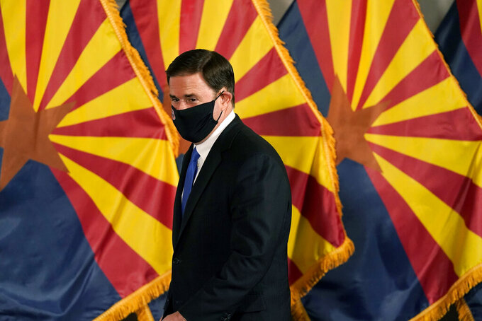 FILE - In this Dec. 2, 2020, file photo, Arizona Republican Gov. Doug Ducey arrives for a news conference to talk about the latest Arizona COVID-19 information in Phoenix. Ducey is prohibiting government mask mandates and allowing bars and nightclubs shuttered for months to open their doors without restrictions. Ducey's move Thursday, March 25, 2021, leaves in place few of the restrictions he implemented to curb the spread of the coronavirus. (AP Photo/Ross D. Franklin, Pool, File)