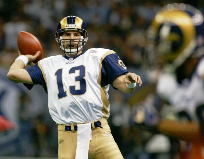 """FILE - In this Feb. 3, 2002, file photo, St. Louis Rams quarterback Kurt Warner looks to pass to Marshall Faulk, right, in the first quarter against the New England Patriots in Super Bowl 36 in New Orleans. The Greatest Show On Turf. """"That team and that era, football kind of saw everyone with a mindset of three yards and a cloud of dust in December and January, and you had to be able to run the football to win was kind of the mantra,"""" says Warner, who entered the Pro Football Hall of Fame in 2017. """"We were one of the first to show you can win throwing first. I guess that is all relative with such an extremely talented team because Marshall ran for almost 1,400 yards. (AP Photo/Doug Mills, File)"""