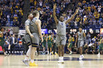 West Virginia guards Jordan McCabe (5), Sean McNeil (22), forward Oscar Tshiebwe (34), and guard Miles McBride (4) celebrate after a score against Baylor during the first half of an NCAA college basketball game Saturday, March 7, 2020, in Morgantown, W.Va. (AP Photo/Kathleen Batten)