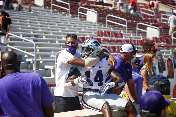 Jon Alexander hugs Kansas State defensive back Tyrone Lewis (14) after his team's 38-35 win over the Oklahoma in an NCAA college football game, Saturday, Sept. 26, 2020, in Norman, Okla. (Ian Maule/Tulsa World via AP)