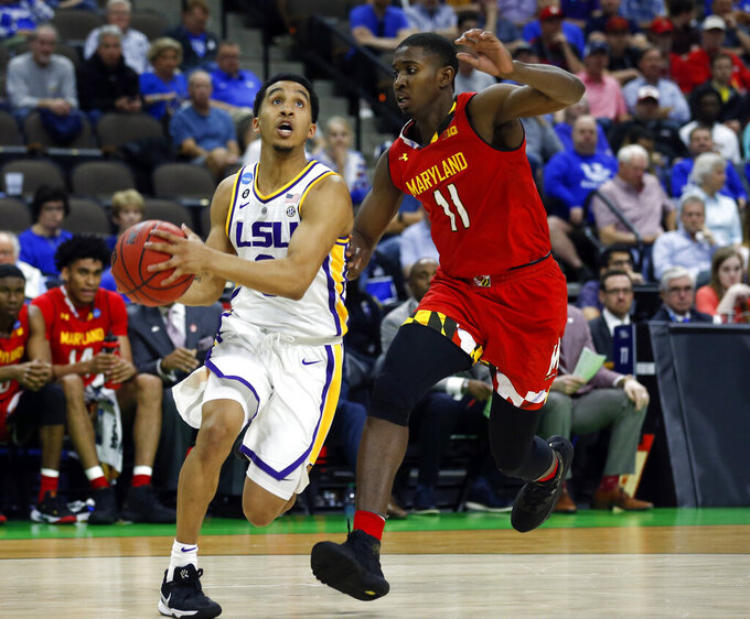 LSU's Tremont Waters, left, goes to the basket past Maryland's Darryl Morsell (11) during the first half of a second-round game in the NCAA men's college basketball tournament in Jacksonville, Fla., Saturday, March 23, 2019. (AP Photo/Stephen B. Morton)