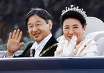 Japanese Emperor Naruhito, left, and Empress Masako wave to spectators during the royal motorcade in Tokyo, Sunday, Nov. 10, 2019.(Naoya Osato/Kyodo News via AP)