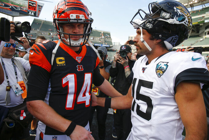 Cincinnati Bengals quarterback Andy Dalton (14) meets with Jacksonville Jaguars quarterback Gardner Minshew (15) after an NFL football game, Sunday, Oct. 20, 2019, in Cincinnati. (AP Photo/Gary Landers)