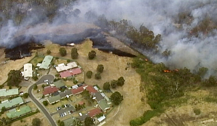 In this image made from video, an aerial scene shows fires burning and smoke rising close to properties in Bundoora, Victoria state, Monday, Dec. 30, 2019. New Year's Eve fireworks in Australia's capital and other cities have been canceled as the wildfire danger worsens in oppressive summer heat, and pressure was building for Sydney's iconic celebrations to be similarly scrapped. (Australian Broadcasting Corporation, Channel 7, Channel 9 via AP)