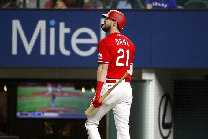 Texas Rangers designated hitter David Dahl looks at the video board while walking to the dugout after striking out during the second inning of the team's baseball game against the Baltimore Orioles in Arlington, Texas, Friday, April 16, 2021. (AP Photo/Roger Steinman)