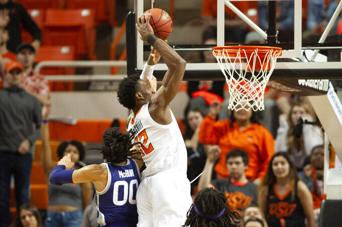 Oklahoma State forward Cameron McGriff (12) dunks while under pressure from Kansas State guard Mike McGuirl (0) during the second half of an NCAA college basketball game in Stillwater, Okla., Wednesday, March 4, 2020. Oklahoma State won 69-63. (AP Photo/Brody Schmidt)