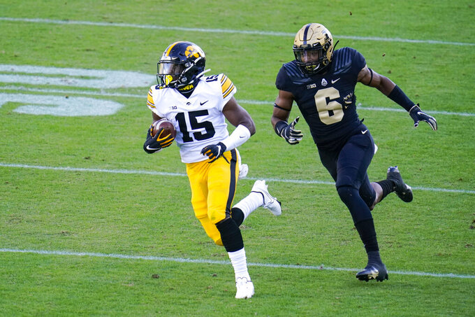 Iowa running back Tyler Goodson (15) runs after catching a pass in front of Purdue safety Jalen Graham (6) during the first quarter of an NCAA college football game in West Lafayette, Ind., Saturday, Oct. 24, 2020. (AP Photo/Michael Conroy)