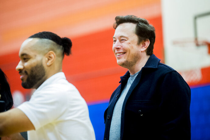 Tech billionaire Elon Musk smiles as he see how many students raise their hands when asked if they know what an engineer is while he and other Tesla officials talk with hundreds of Flint students on Friday, March 22, 2019 a Doyle-Ryder Elementary School in Flint, Mich. The Elon Musk Foundation announced in December it was giving about $424,000 to help provide laptops as the city recovers from a crisis with lead-tainted water .    ) Jake May | MLive.com/The Flint Journal via AP)